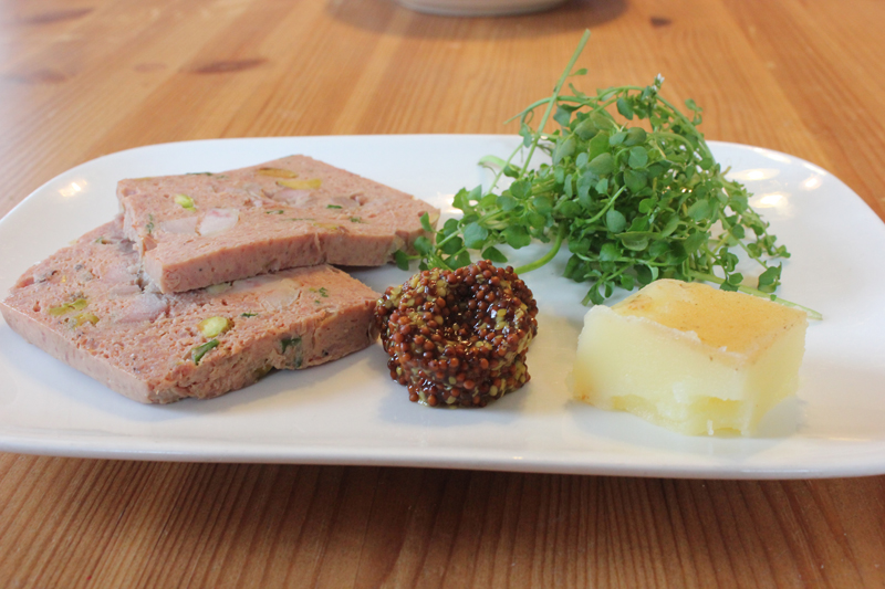 "Chicken liver mousseline in a ""Schmaltz spread"" plate setup (a manner in which diners will be able to order from the menu), shown here to include a wild greens salad, wild whole-grain mustard and schmaltz."