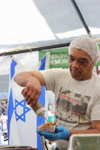 With an Israeli flag hanging at his food tent, Erich Hooper prepares a dish for a customer at the 2016 Hessler Street Fair.