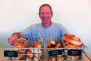 Bialy's Bagels owner Mark Osolin stands behind his finished products, while other bagels rest in various stages of production, from baking in the oven to cooling on the pan.