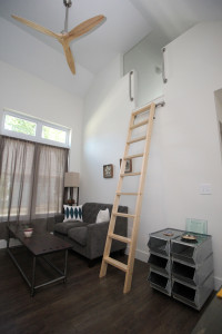 A movable ladder is used to reach both the loft bedroom, shown above, and storage units located above the bathroom entrance at DSCDO's Tiny House.