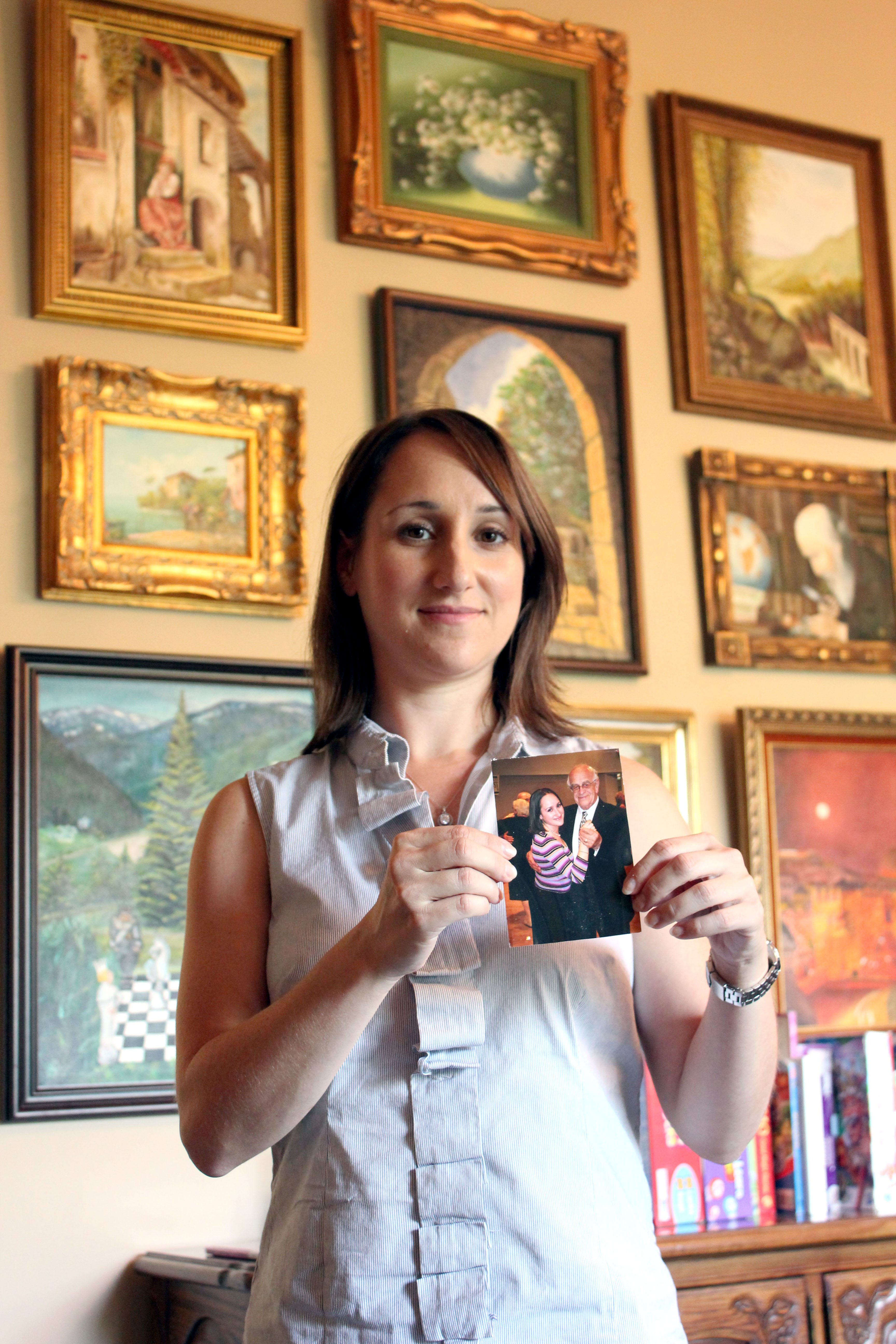 Julie Kronenberg holds a photo of her dancing with her grandfather, Jacob Hennenberg, a Holocaust survivor during a 2001 Kol Israel dinner held in honor of him. Behind her are several of her grandfather's paintings, and the Beachwood house in which she now lives was once her grandparents' home.