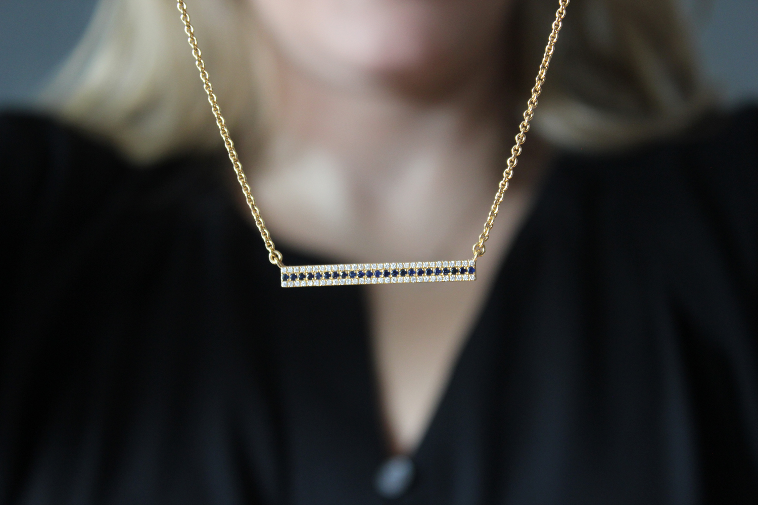 An 18-karat yellow gold diamond and sapphire bar necklace made by Synenberg.