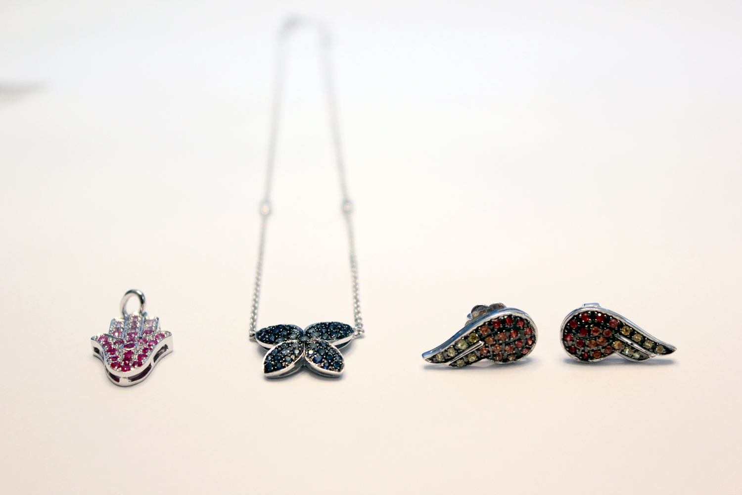 From left: Silver-plated ombré pink sapphire hamsa hand pendant; 18-karat gold ombré of sapphires butterfly necklace; and colored sapphire wing earrings, all made by Synenberg.
