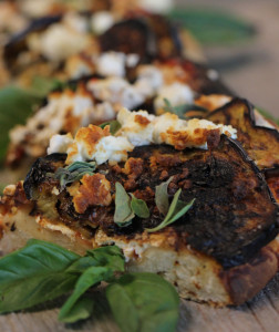 An eggplant and feta wood-fired pizza with fresh mint and tomato sauce.