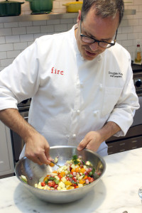 Katz prepares an Israeli salad in his kitchen.
