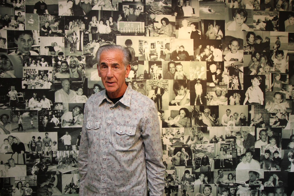 Art collector Mike Belkin in front of a wall-sized photo collage his wife, Annie, assembed. The collage, located on the lower level of the couple's Geauga County home, includes pictures of familly and friends.