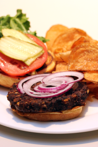 Exploration's vegetarian black bean, chipotle and corn burger with lettuce, tomato, onion and pickle on a challah bun, served with house chips.