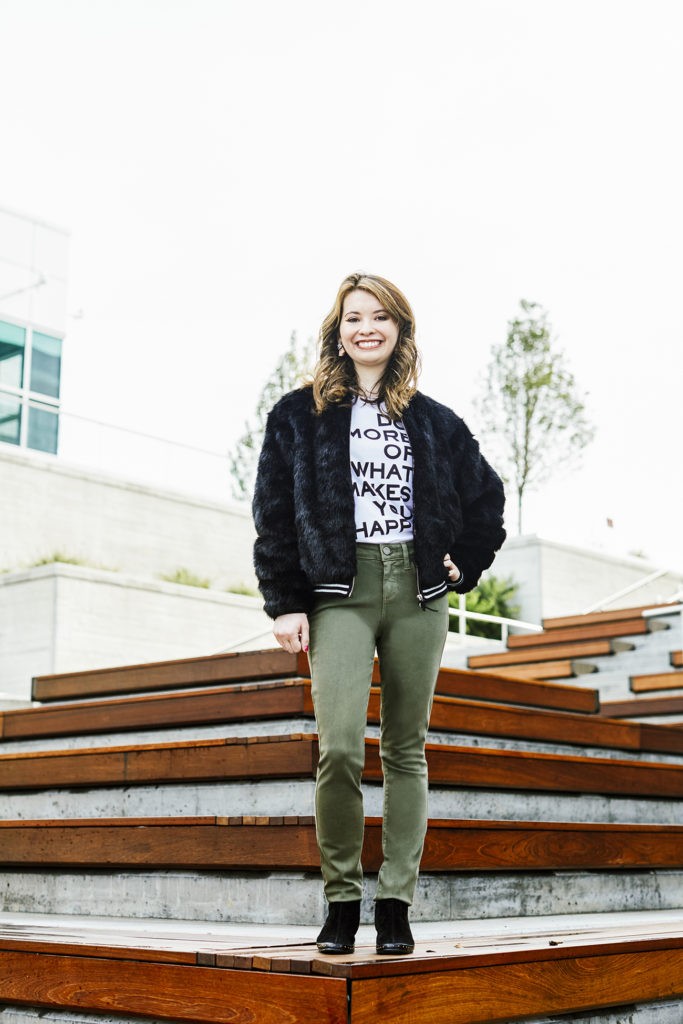 Susan wears a faux fur bomber jacket by Black Orchid, white, graphic fitted T-shirt by Zadig & Voltaire and mid-rise skinny denim in olive by Paige, all from Fringe Boutique in Moreland Hills. Black booties by Magdesians are her own.