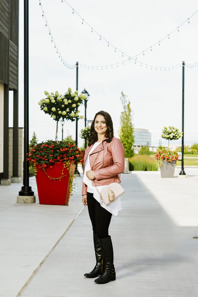 "Rachael wears ""Pheifer"" pants by Bailey 44, white tank-top by Susana Monaco, and pink leather jacket and rose gold tassle purse, both by Ted Baker, all from Laura of Pembroke. Black boots by Nine West are her own."