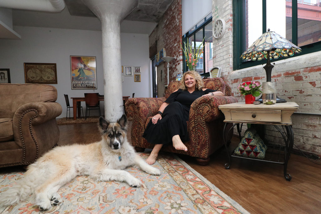 Heidi DuBois and her German shepherd-Akita mix, Boozer, who were among the first residents at Worthington Yards, relax in the living room of her fifth-floor apartment.