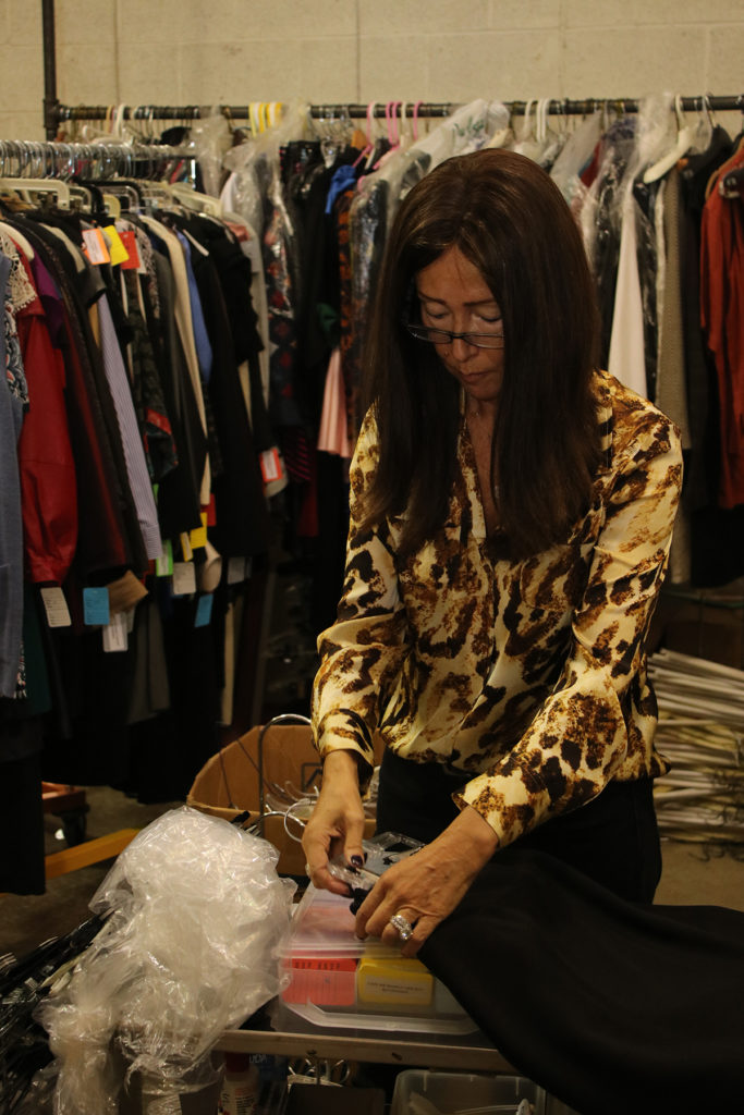 Michele Kaminsky, co-vice president of this year's Designer Dress Days, sorts clothing. Photo by Michael C. Butz
