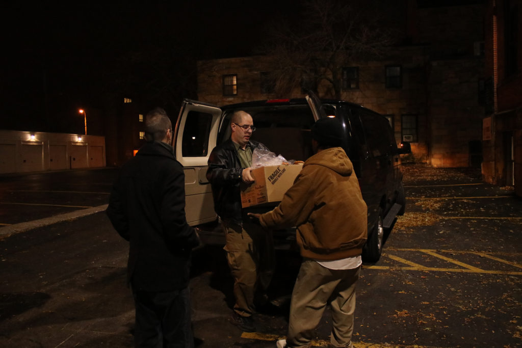 Brett Lipton hands over a box of sandwiches to a representative at St. Malachi Parish in Cleveland while Shaun Friedman holds open the van door.